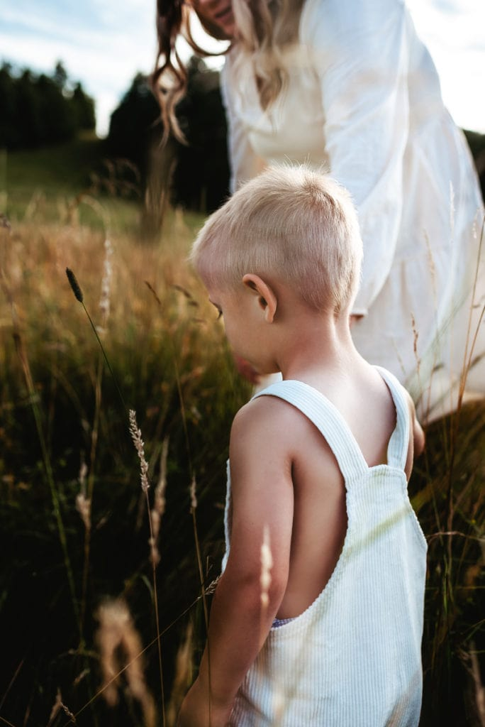 Family Photography, a young boy holds onto his mothers hands as they walk through tall grass outside.