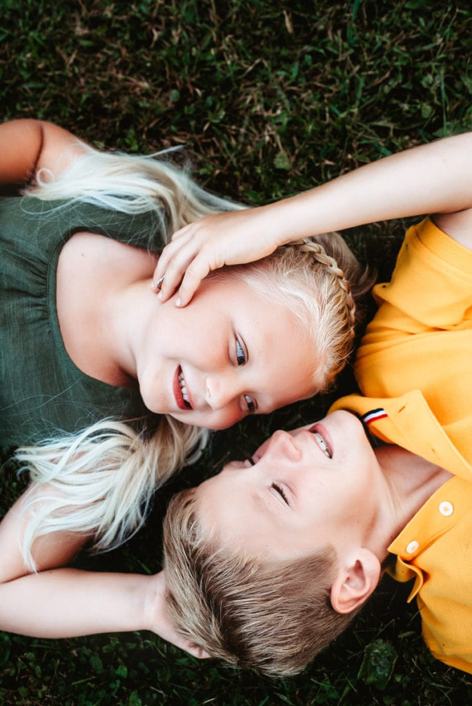Family Photographer, a young brother and sister lovingly lay in the grass smiling together