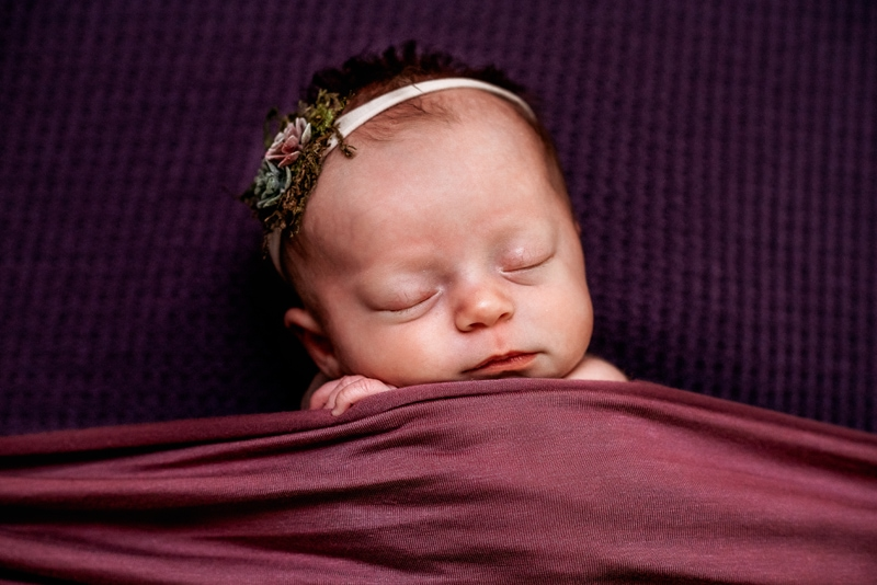 Newborn Photography, a baby lays snuggled happily beneath a maroon blanket